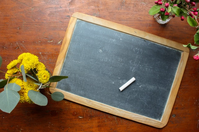 A small chalkboard next to a vase of yellow flowers by RK on unsplash