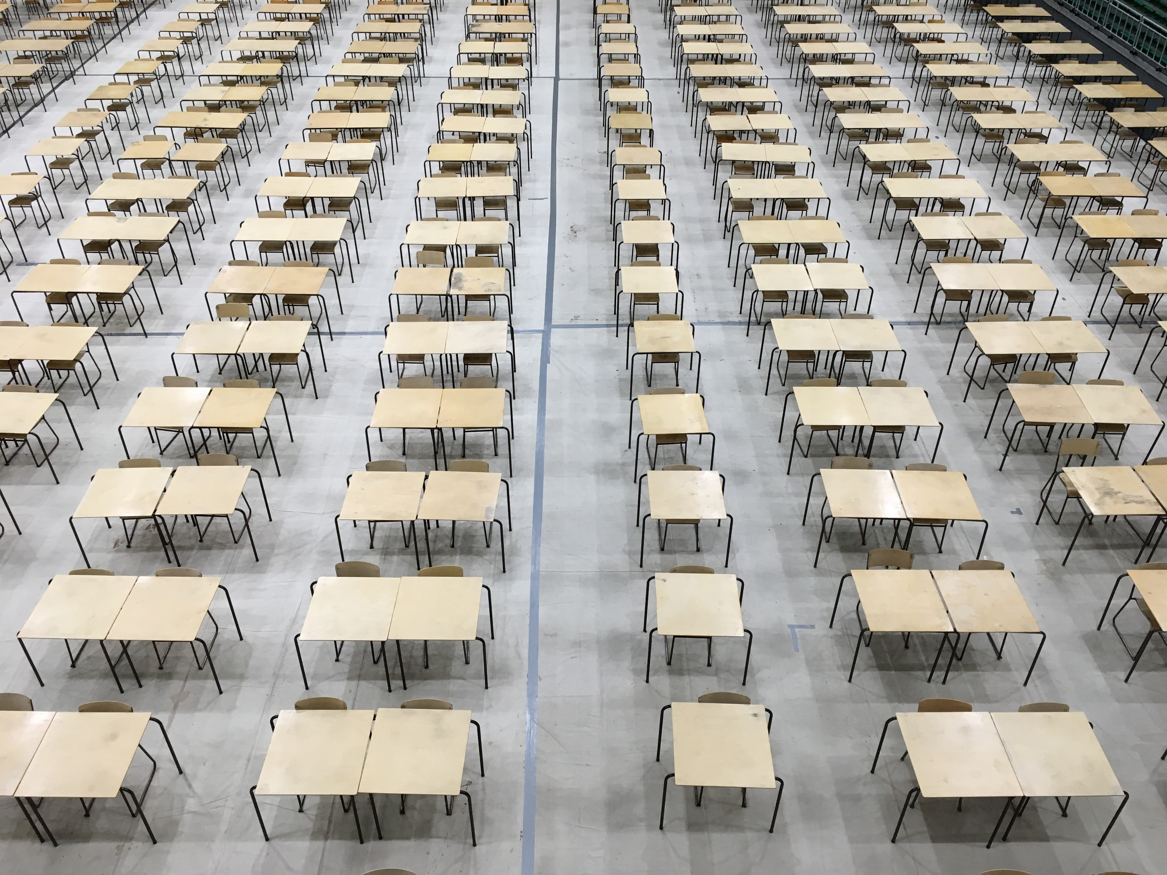 Rows of desks and chairs in an exam hall